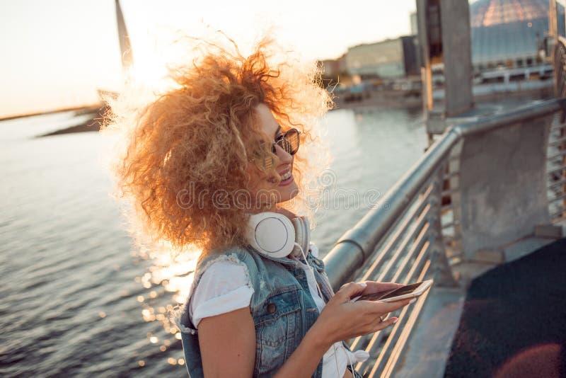 Het in meisje met grote hoofdtelefoons en zonnebril op een stadsgang, jonge vrouw gebruikt een smartphone royalty-vrije stock foto