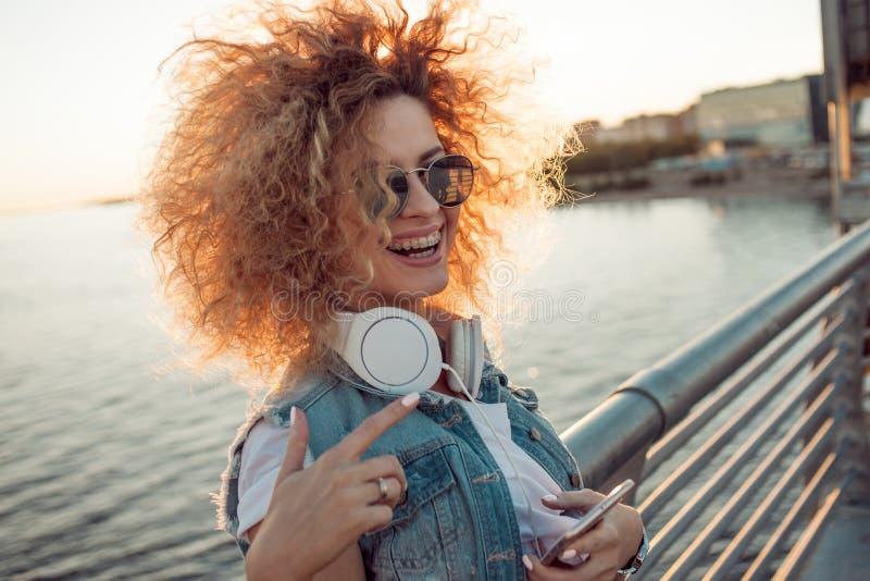 Het in meisje met grote hoofdtelefoons en zonnebril op een stadsgang, jonge vrouw gebruikt een smartphone stock afbeeldingen