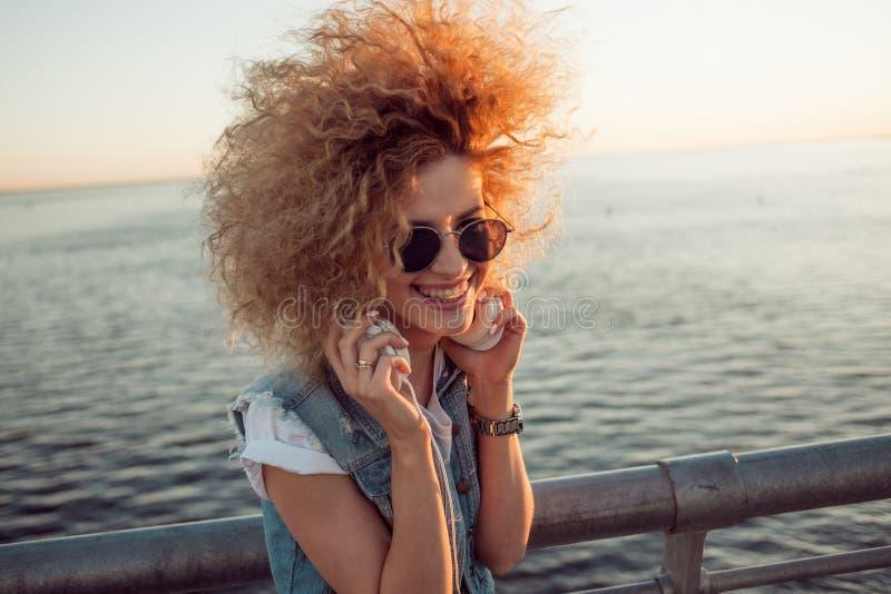 Het in meisje met grote hoofdtelefoons en zonnebril op een stadsgang, sluit omhoog stock afbeelding