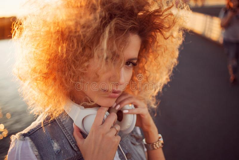 Het in meisje met grote hoofdtelefoons op een stadsgang, sluit omhoog stock afbeeldingen