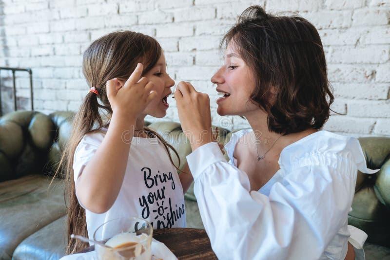 Het meisje met haar moeder eet havermeelkoekjes en heeft pret stock afbeeldingen