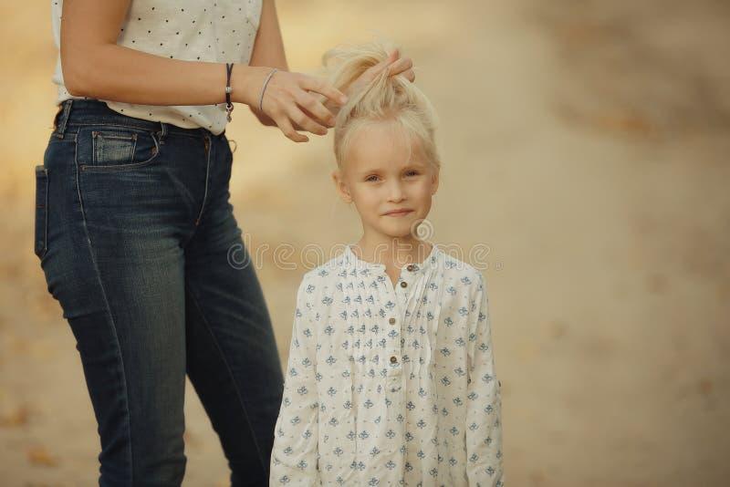 Het meisje is met haar moeder op de herfstgebied royalty-vrije stock afbeelding