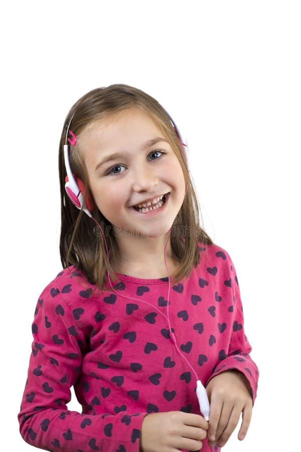 Het meisje met hoofdtelefoons luistert muziek royalty-vrije stock afbeelding