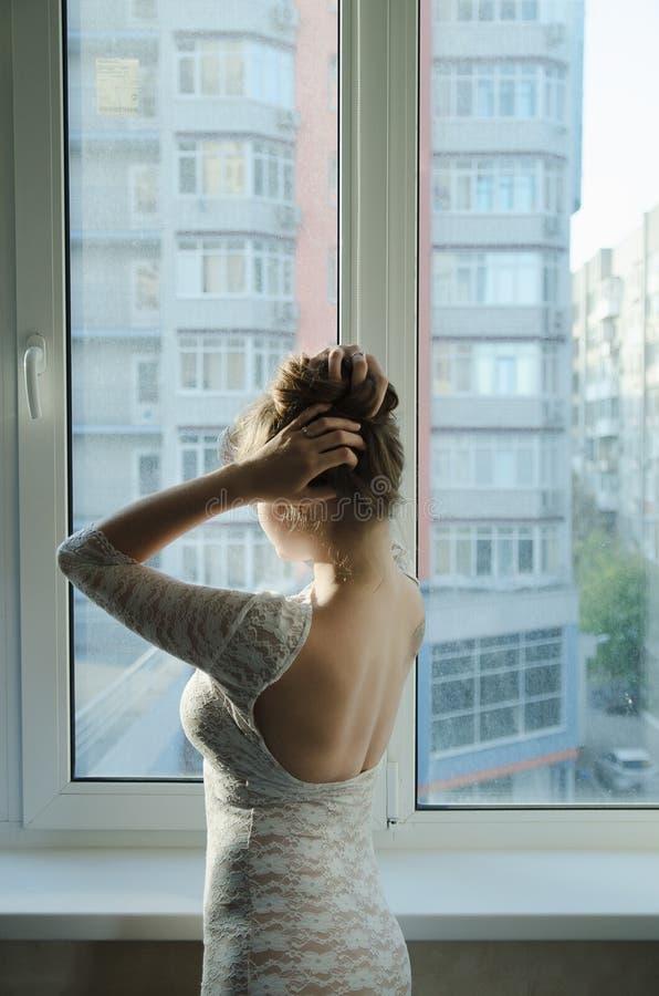 Het meisje met lang bruin haar in een witte kleding die zich bij het venster van de rug bevinden en verbetert kapsel royalty-vrije stock fotografie