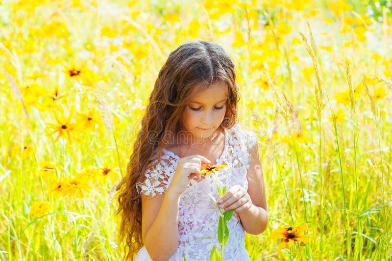 Het meisje met lang haar in een witte kleding verheugt zich in een gebied met bloemen royalty-vrije stock afbeeldingen