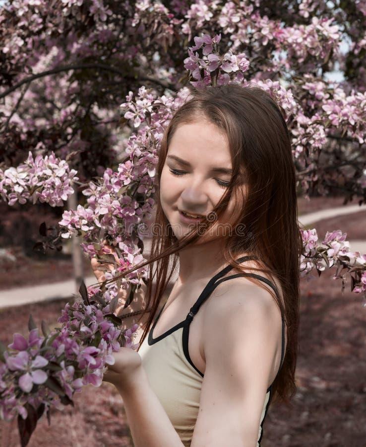 Het meisje met lang haar en gesloten ogen bevindt zich dichtbij een bloeiende tak van een Apple-boom, een jonge vrouwenglimlachen stock fotografie