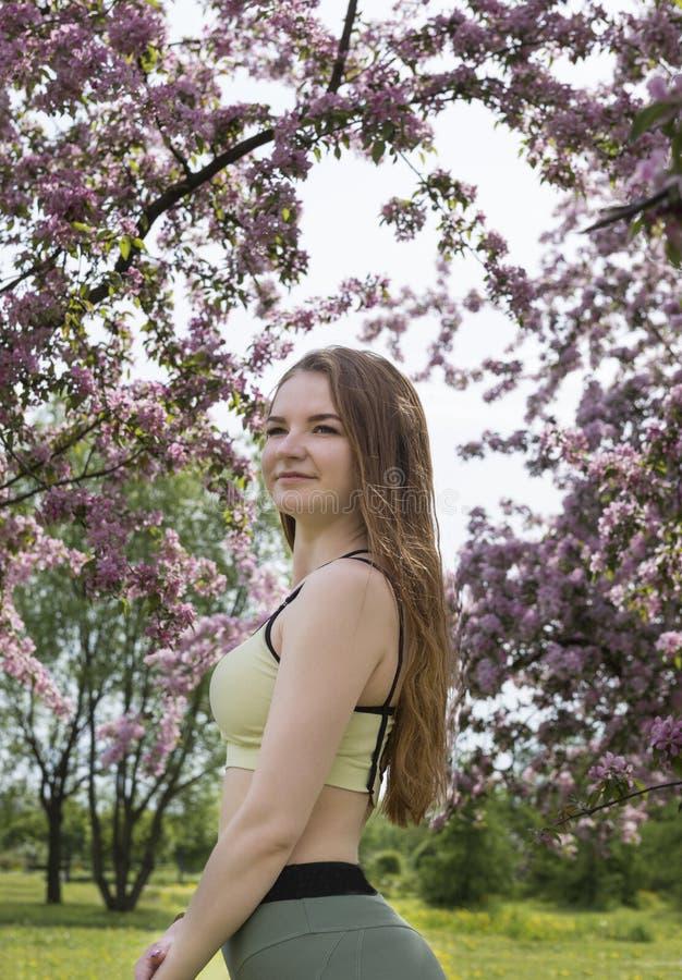Het meisje met lang haar in sporten kleedt tribunes in Park op de achtergrond van bloeiende bomen, bloeiende Apple-boomgaard, roz stock foto's