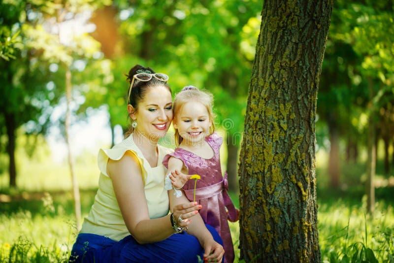 Het meisje met moeder kijkt een gele bloem op de groene achtergrond stock fotografie