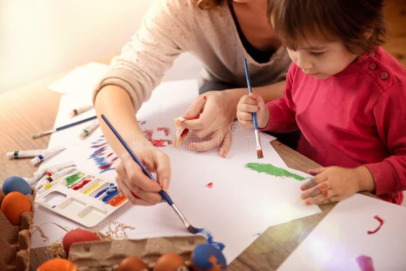 Het meisje met moeder maakt paaseieren royalty-vrije stock foto