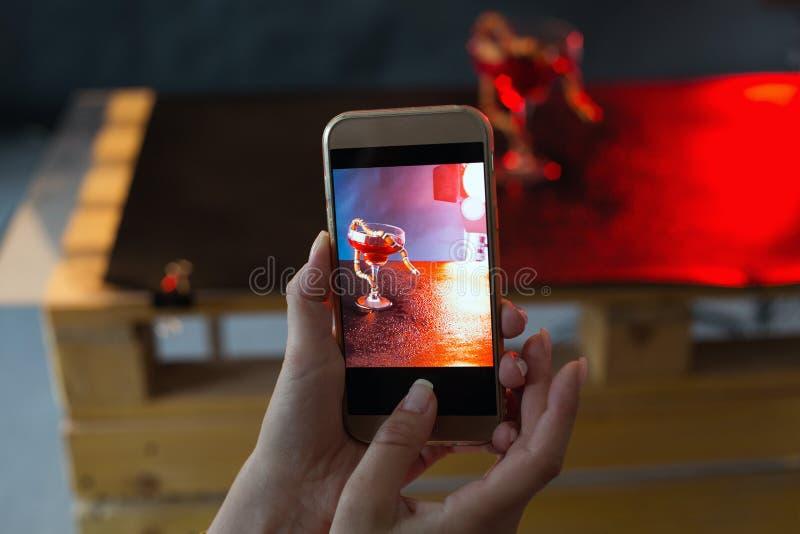 Het meisje met mooie manicure fotografeert een slang in een glas tegen een donkere achtergrond de foto via telefoon stock fotografie