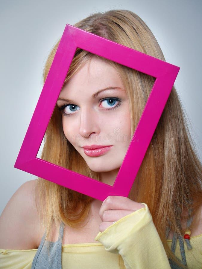 Het meisje met mooie ogen houdt een roze kader bij royalty-vrije stock foto's