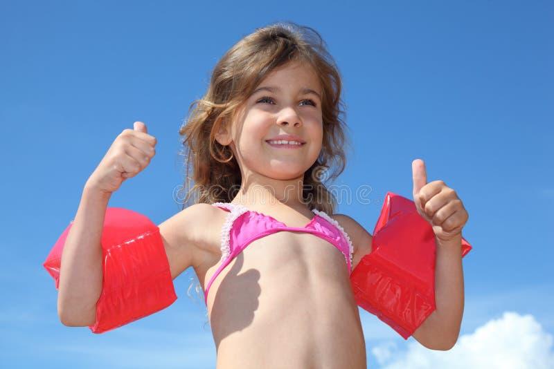 Het meisje met opblaasbare armbanden beduimelt omhoog stock fotografie