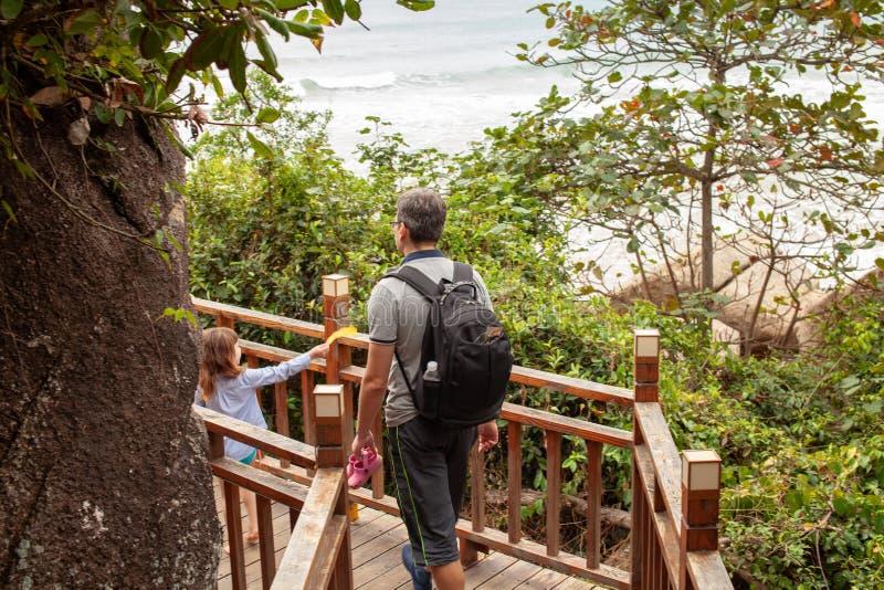 Het meisje met papa gaat op een houten ladder in de tropische bergen stock afbeeldingen