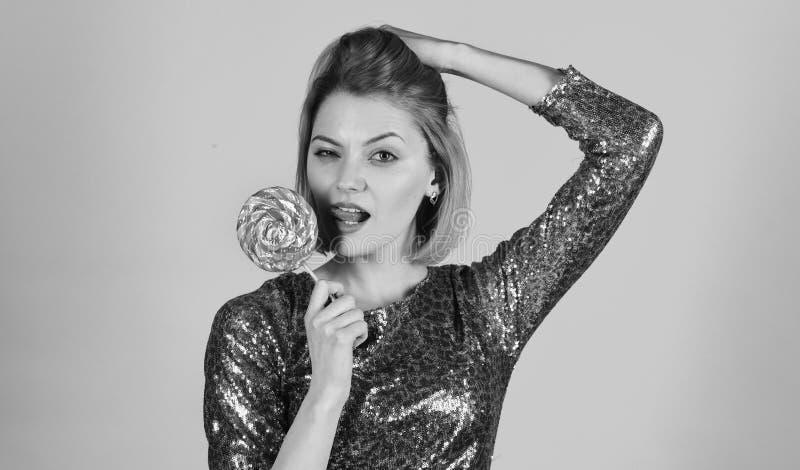 Het meisje met sexy verleidelijk gezicht eet kleurrijk suikergoed houdend haar haar De vrouw houdt lolly op blauwe achtergrond Me stock fotografie