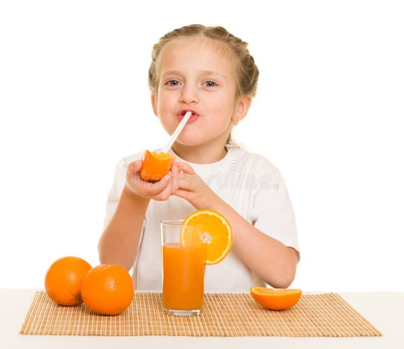 Het meisje met sinaasappelen drinkt sap met stro royalty-vrije stock afbeeldingen