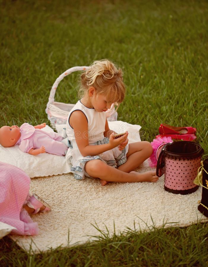 Het meisje met smartphone zit op dekking op groen gras royalty-vrije stock foto