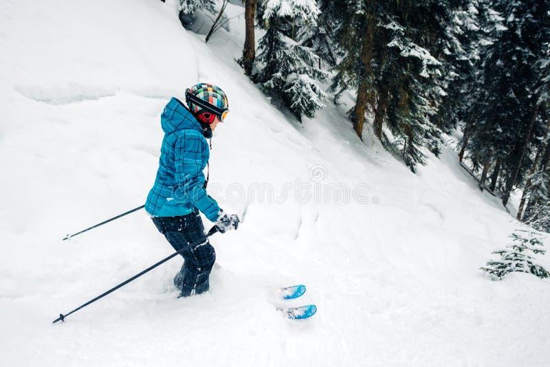 Het meisje met speciaal skimateriaal berijdt en springt zeer snel in het bergbos royalty-vrije stock afbeelding
