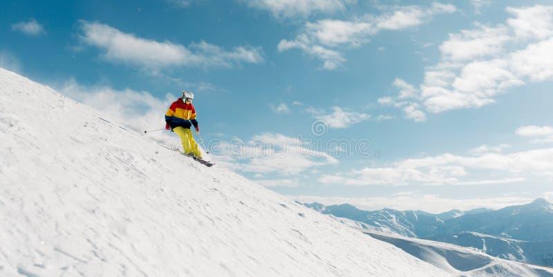 Het meisje met speciaal skimateriaal berijdt zeer snel in de bergheuvel stock foto's