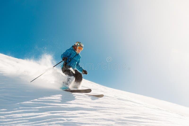 Het meisje met speciaal skimateriaal berijdt zeer snel in de bergheuvel royalty-vrije stock afbeelding