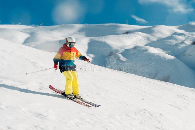 Het meisje met speciaal skimateriaal berijdt zeer snel in de bergheuvel royalty-vrije stock foto's