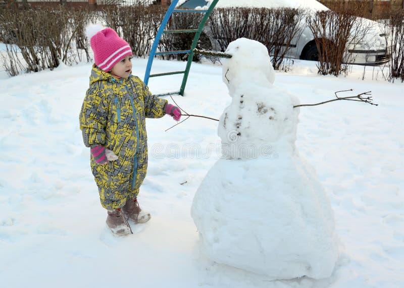 Het meisje met verbazing bekijkt een sneeuwman stock fotografie