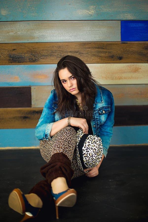 Het meisje met vlechten in jeans past en in een luipaardhoed aan stock fotografie