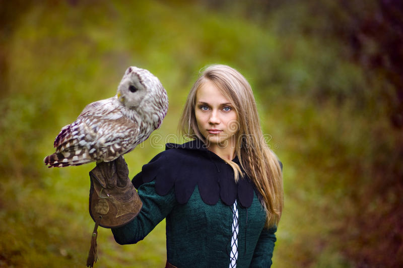 Het meisje in middeleeuwse kleding houdt een uil op haar wapen stock afbeelding