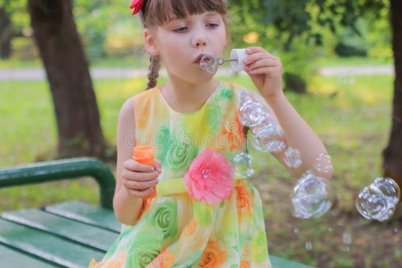 Het meisje in mooie kledingszitting blaast bellen royalty-vrije stock afbeeldingen
