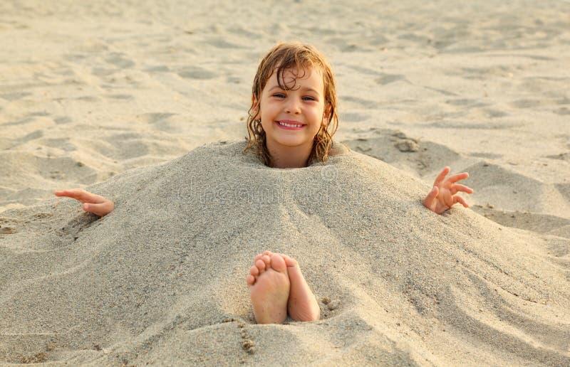 Het meisje na het zwemmen wordt begraven in zand op strand stock afbeeldingen