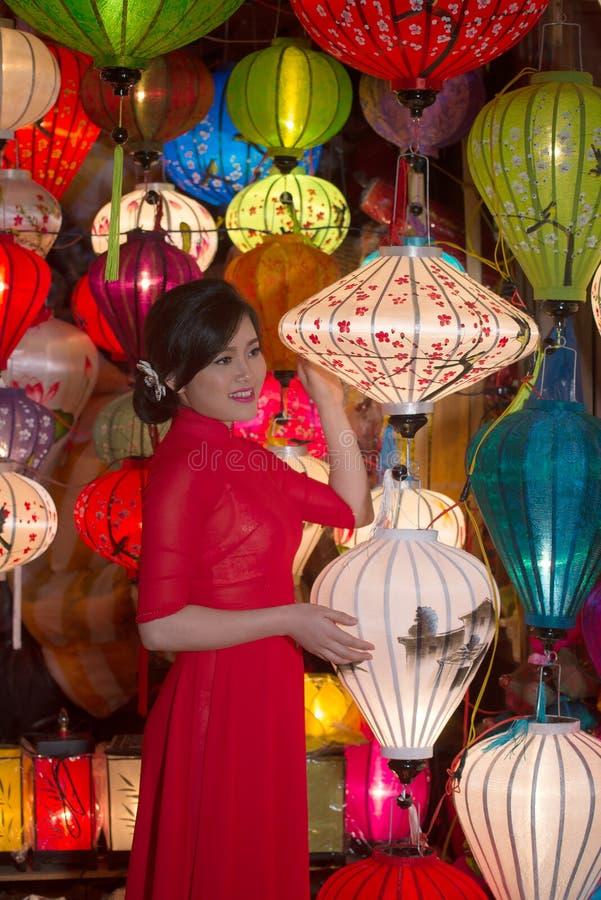 Het meisje in nationale kleren verkoopt Chinese lantaarns in een herinneringswinkel Hoi, Vietnam stock foto
