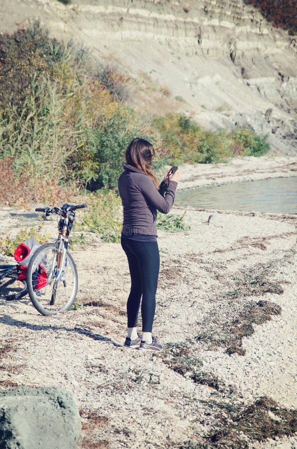 het meisje neemt beelden op de kustlijn stock foto