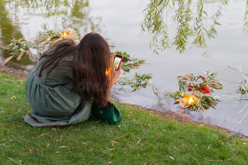 Het meisje neemt beelden van een kroon van bloemen in het meer, uitvoerend de traditionele rite van de vakantie van Ivan Kupala stock foto's