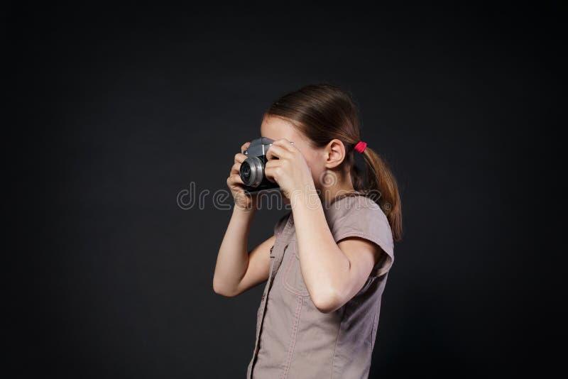 Het meisje neemt foto met uitstekende camera bij zwarte achtergrond stock foto
