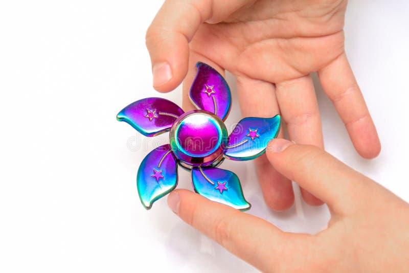 Het meisje om met Fidget Spinner in zijn handen te spelen, het concept het verlichten van spanning, ontwikkelt een kleine handwis stock fotografie
