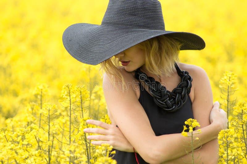 Het meisje omhelst zich en raakt zacht de bloem royalty-vrije stock afbeelding