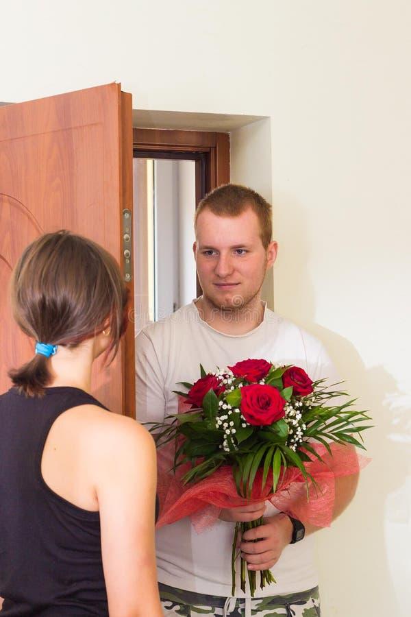 Het meisje ontmoet vriend met bloemen dichtbij de deur royalty-vrije stock fotografie