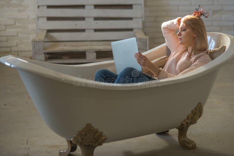 Het meisje ontspant in badkuip met laptop houdt blog Het vrouwenwerk aangaande computer in huisbad Behendige zaken en mededeling  royalty-vrije stock afbeeldingen