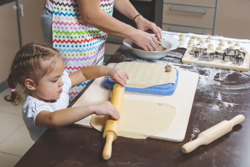 Het meisje ontwikkelt het deeg, terwijl haar moeder het gehakt voor het koken van bollen beweegt stock foto