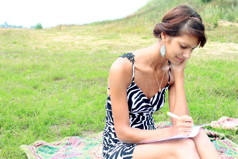 Het meisje op de aard van een laptop geval stock afbeelding