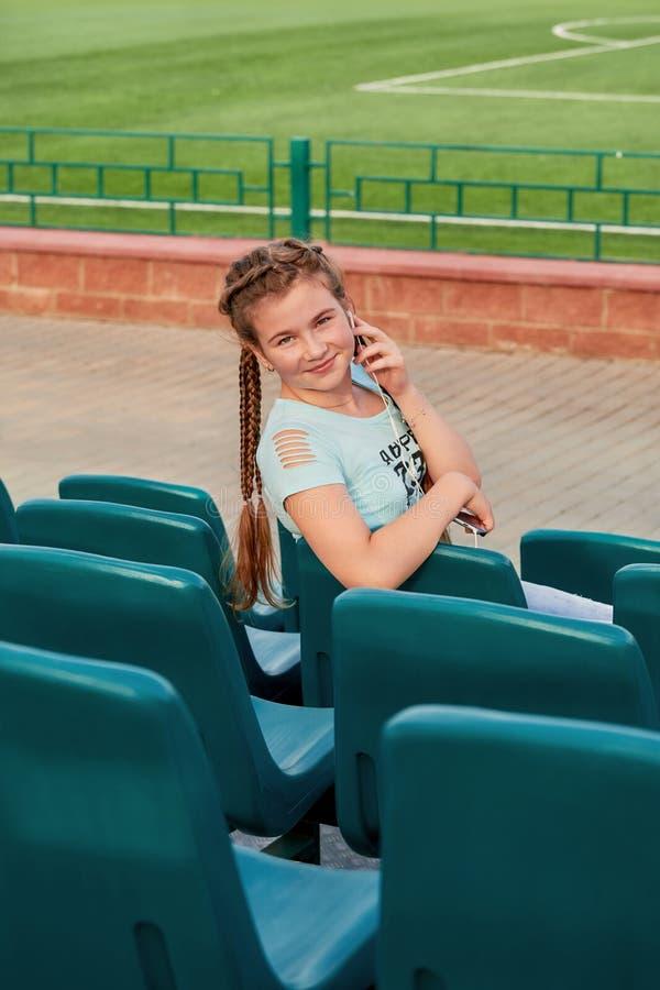 Het meisje op de zetel in de tribunes Een jong helder meisje houdt van sporten stock foto's