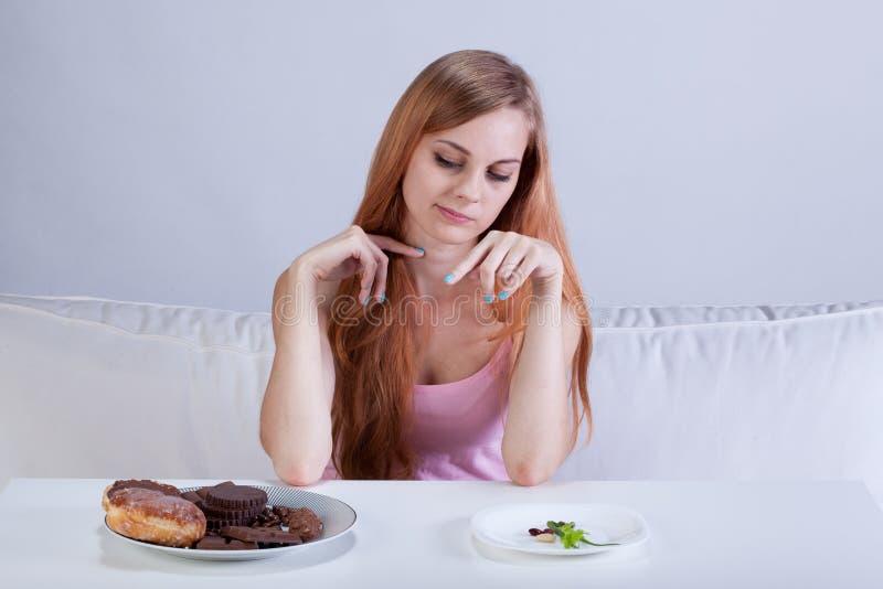 Het meisje op dieet wil sommige snoepjes royalty-vrije stock foto