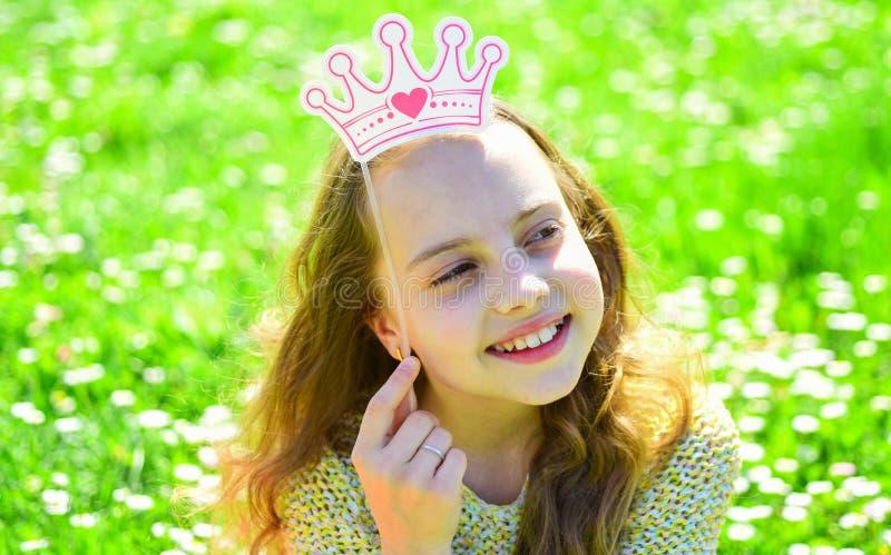 Het meisje op dromerig gezicht besteedt in openlucht vrije tijd Kind het stellen met kartonkroon voor fotozitting bij weide Het m royalty-vrije stock afbeeldingen
