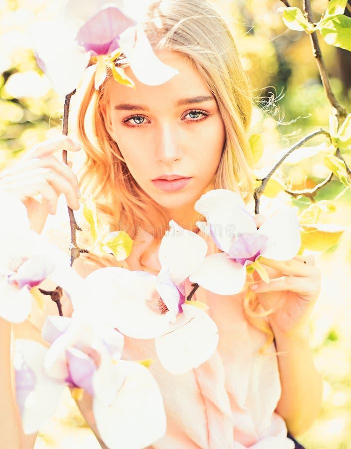Het meisje op dromerig gezicht, teder blonde dichtbij magnolia bloeit, aardachtergrond De jonge vrouw geniet van bloemen in tuin  royalty-vrije stock fotografie