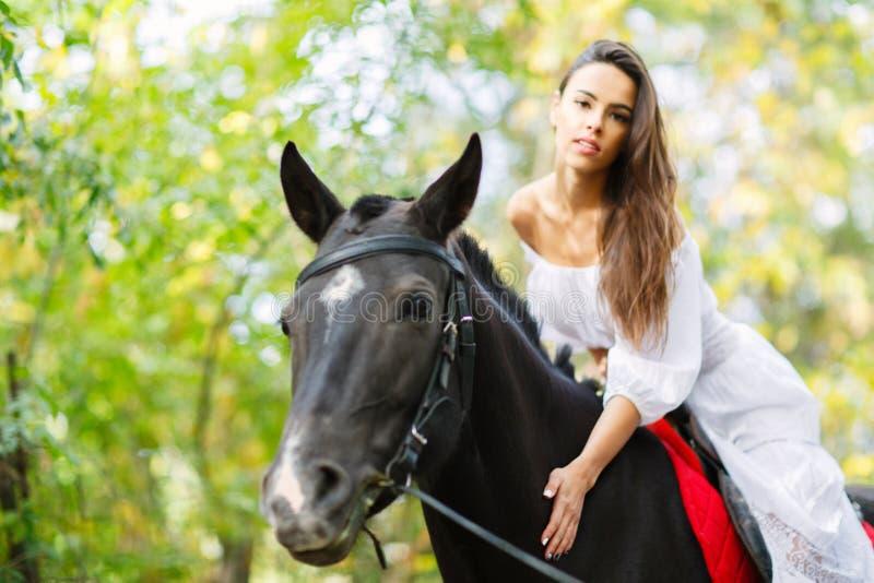 Het meisje is op een paard buiten royalty-vrije stock foto