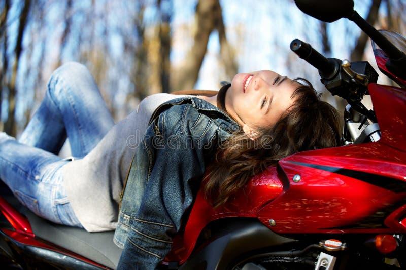 Het meisje op een rode motorfiets stock foto