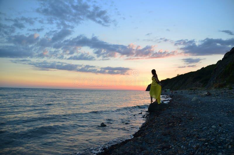 Het meisje op een steen dichtbij het overzees royalty-vrije stock afbeeldingen