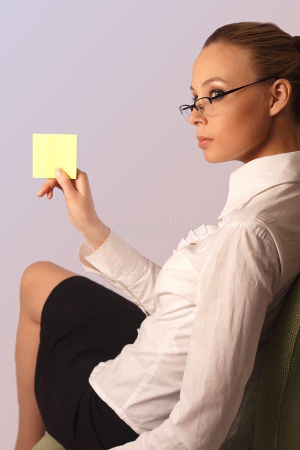 Het meisje op een stoel houdt een lege sticker stock fotografie
