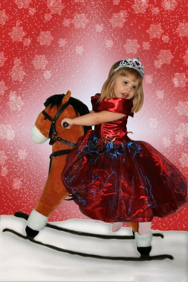 Het meisje op een stuk speelgoed paard stock fotografie