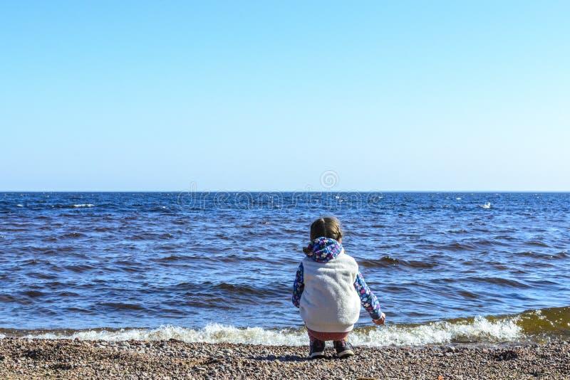 Het meisje op een verlaten strand zit en verzamelt stenen en shells tegen de blauwe hemel en de mooie golven van het overzees stock afbeelding