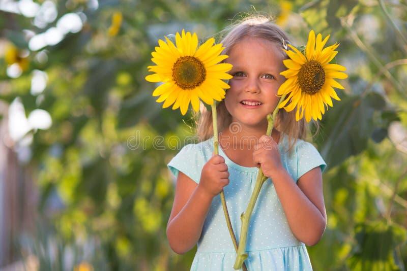 Het meisje op het gebied van zonnebloemen stock afbeeldingen